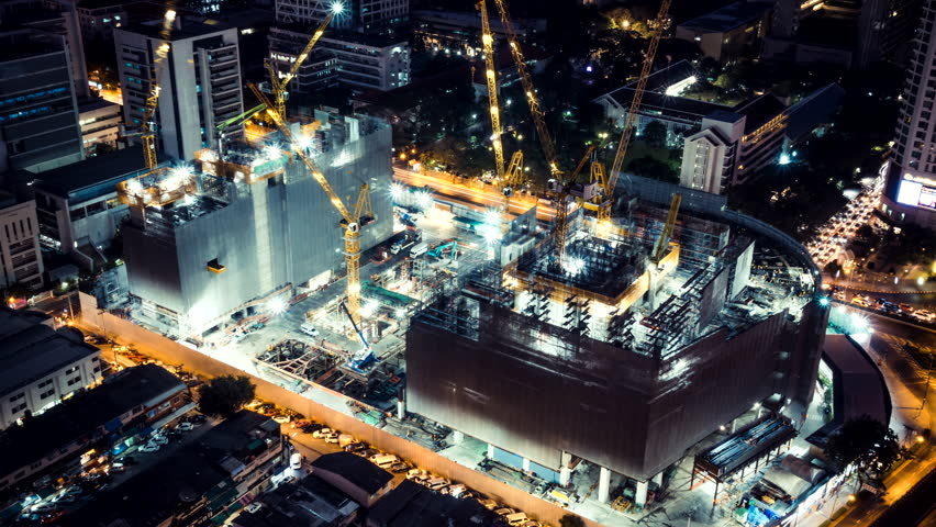 Time-lapse of construction site at night with light trails of traffic in the city, top view. Advanced building technology, busy metro downtown cityscape, or developing industrial country concept. | Shutterstock HD Video #1008451273
