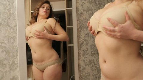 Reflection in mirror of the young woman with weight problems in lingerie touching her belly, stomach and studying her body.
