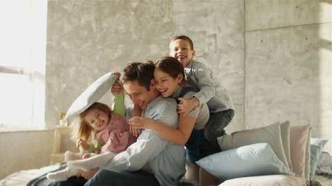 A young father and three children embrace sitting on the bed. Happy fatherhood. Father's Day.