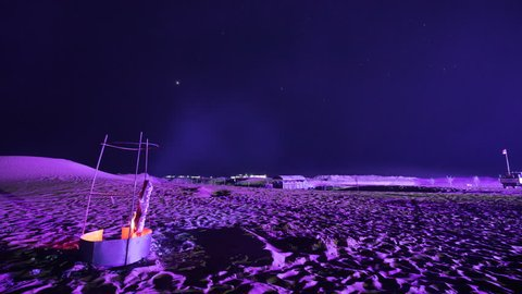 A beautiful high quality video of moving stars from the Gobi Desert. Bright stars are moving through the sky with a burning and sparkling bonfire on the foreground.