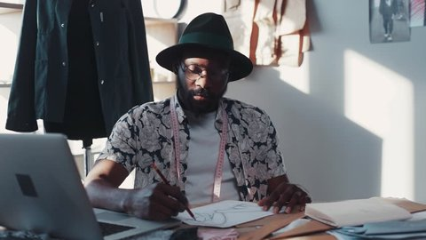 Extravagant, fashionable hipster-like designer creates a new fashion collection. Modern workplace. Piece of art, creative process. Working hard. Male portrait