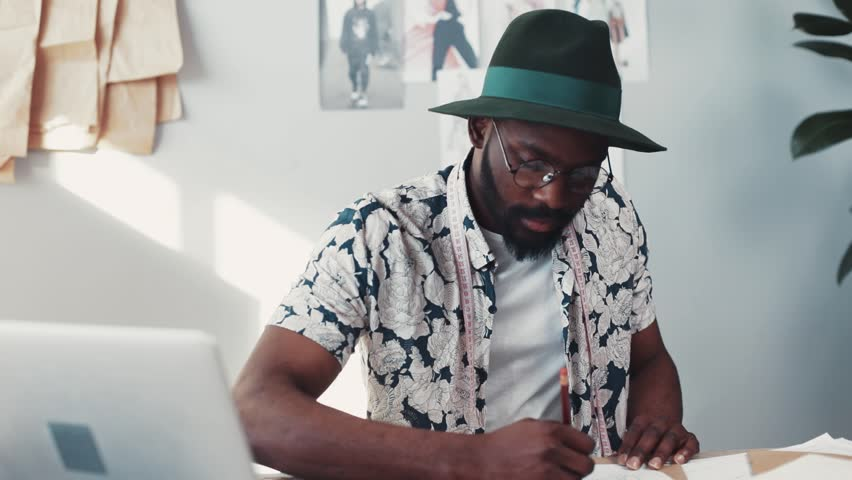 Young talented designer sketching out his new fashion collection, while sitting in a cozy, light studio. House plants, fashion sketches, mannequin on the background. Male portrait, slow motion | Shutterstock HD Video #1008476803