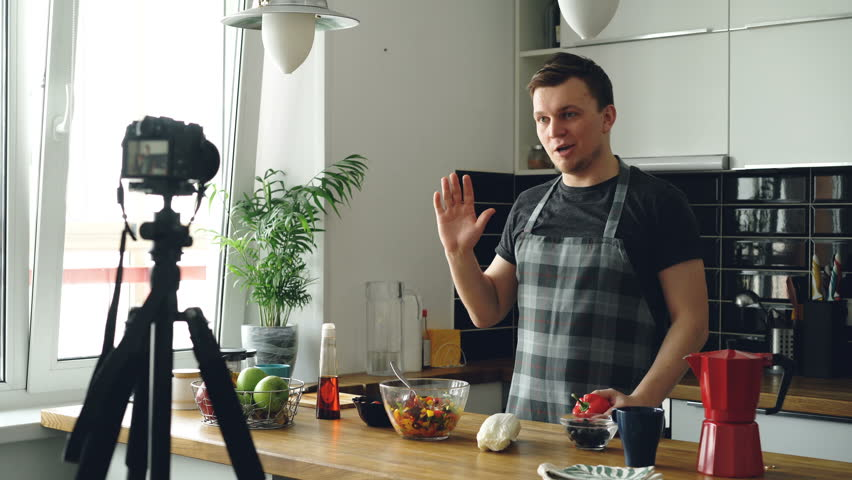 Handsome guy recording video food vlog about healthy cooking on digital camera in the kitchen at home. Vlogging and social media concept