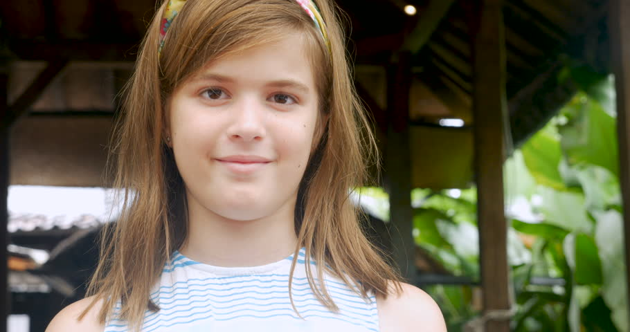 Portrait of a cute 11 - 12 year old girl with a headband smiling and looking at the camera | Shutterstock HD Video #1008482203