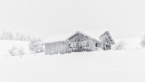Soft gentle falling snow video overlay image of rustic mountainside log cabin in deep snow cover in winter solitude