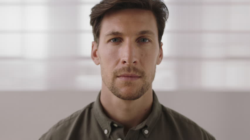 close up portrait of young entrepreneur man looking serious pensive at camera slow motion #1008512233