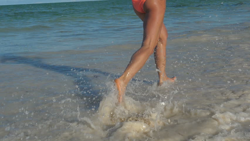 SLOW MOTION Running athletic thin girl in shallow water. young woman with a slender figure. Makes a run along the sea coast. Camera stabilizer shots. | Shutterstock HD Video #1008512293