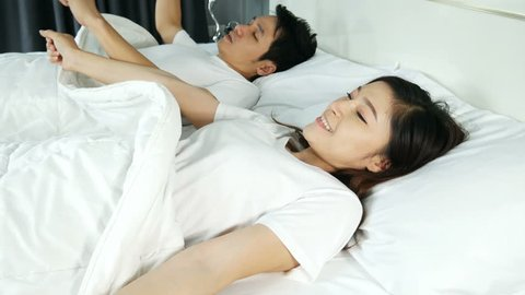 4k of young couple sleeping on a comfortable bed in bedroom at home