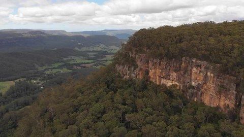 Australia Aerial footage of sandstone mountain escarpment cliffs along valley - NSW, Australia