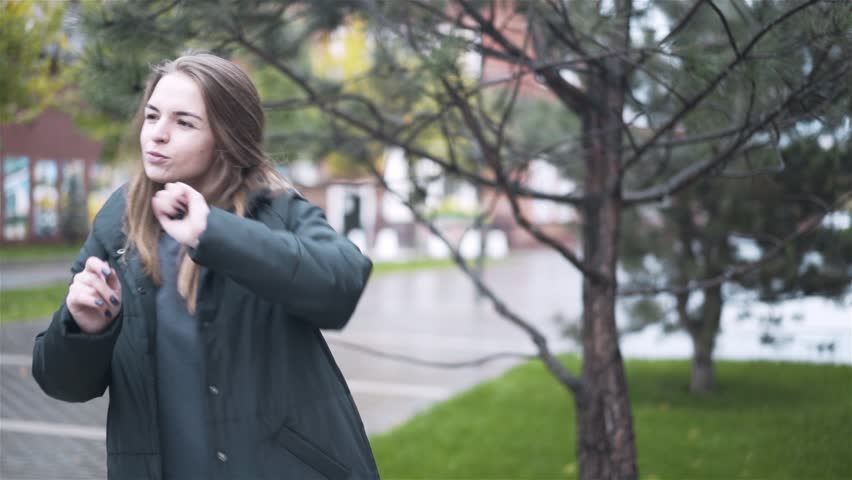 Happy young woman with fair hair wearing a coat and holding a bag is dancing in an autumn street. Handheld slow motion medium shot | Shutterstock HD Video #1008543403