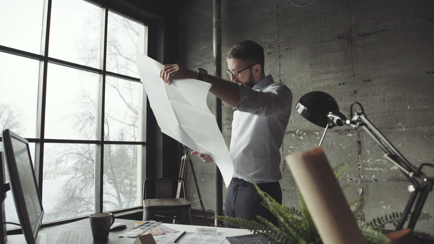 Bearded man (hipster) standing faces to panoramic window and looks at blueprints. Young architect in stylish loft office works with documents. Creative architect thinking on the big drawings. | Shutterstock HD Video #1008550813
