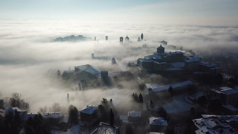 Bergamo, Italy. Drone aerial view of an amazing landscape of the fog rises from the plains and covers the old town