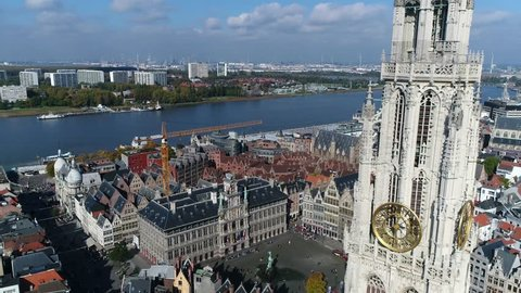 Urban aerial Antwerp backwards flight past The Cathedral of Our Lady tower in Dutch Onze-Lieve-Vrouwekathedraal is Roman Catholic cathedral Antwerp Belgium also showing Scheldt river 4k quality