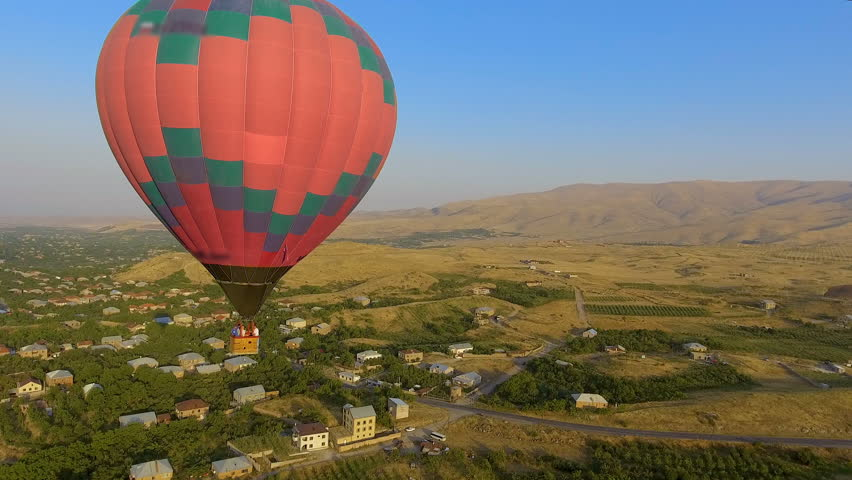 Huge multicolored hot air balloon flying over Armenian village, landscape