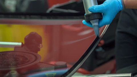 A mechanic is applying some black glue on the front window of the car and then he will stick it together with the front part of the car. A car window was broken.