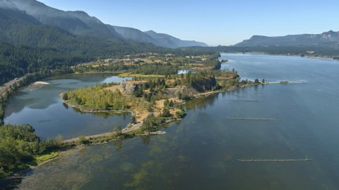 Aerial dolly shot of a small peninsula in the Columbia River Gorge with clear waters and green trees on a hot summer day with beautiful mountains along each side