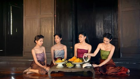 Group of Royal court concubine  woman girl with Thai traditional dress costume relax and enjoy Thai Dessert on wood table