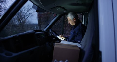 4K Delivery driver checking the paperwork in his van on early morning shift