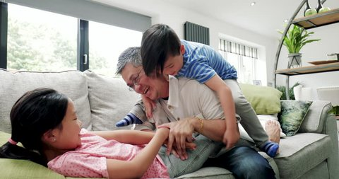 Little boy and his sister are being tickled by their father on the sofa at home.