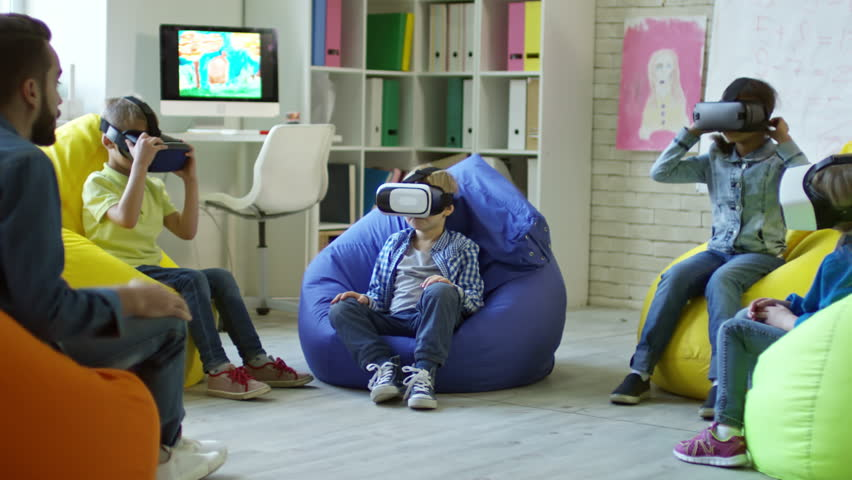 Little boys and girls sitting on colorful bean bag chairs and watching educational video in VR glasses while male teacher talking to them | Shutterstock HD Video #1008653863