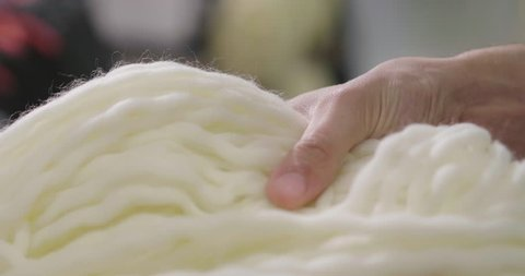 Close up of a hand touching raw, warm and soft wool. Concept of: tenderness, softness, warm, clothes.