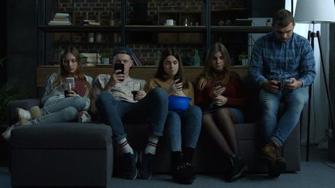Group of young friends phubbing each other while sitting in a row on the couch in domestic room. Busy teenagers using smart phones with disinterest on each other. Technology and smart phone addiction.