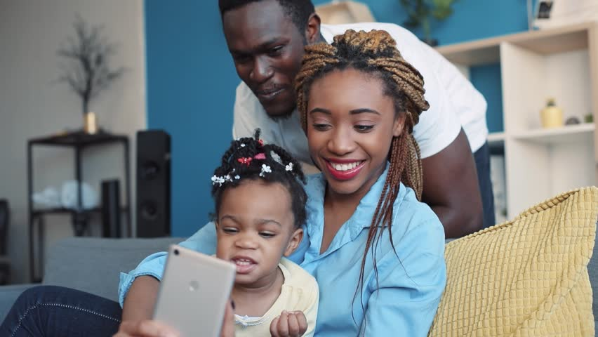 Happy young family taking selfie, brightly smiling straight to phone's camera. Family portrait, childhood memories. Close up view, camera stabilizer shot | Shutterstock HD Video #1008693133