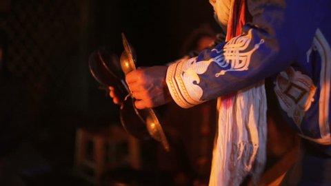Tight shot of man in Moroccan dress playing arabic doumbek, darbuka.
