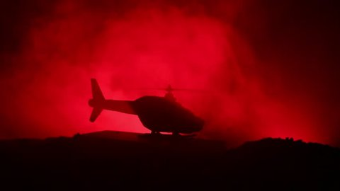 Slider shot. Silhouette of military helicopter ready to fly from conflict zone. Decorated night footage with helicopter starting in desert with foggy toned backlit. Selective focus. War concept