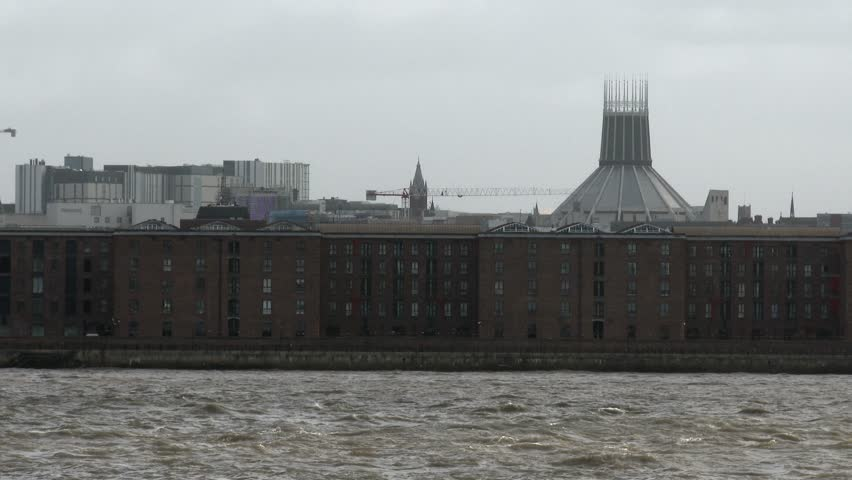 The red brick Albert Dock warehouse next to the River Mersey estuary, with the Liverpool Metropolitan Cathedral in the distance.