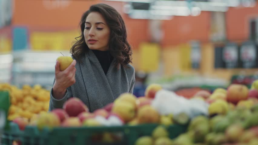 Attractive young woman choosing apple at fruit vegetable supermarket marketplace  | Shutterstock HD Video #1008728873