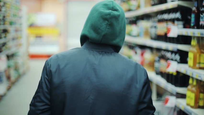 Portrait man steals bottle of alcohol in supermarket go away shot behind shoplifting larceny technology crime store theft criminal customer illegal retail poor looting lifting security shop consumer | Shutterstock HD Video #1008755363