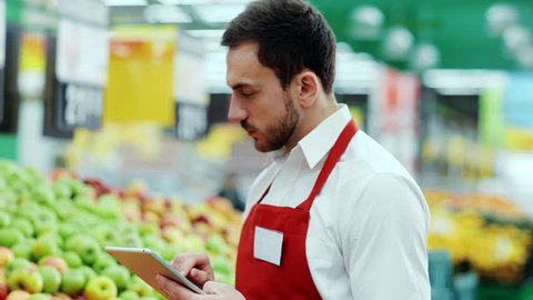 Close up face serious seller consultant using digital tablet in supermarket near fruit worker internet communication man holding connection job organic market store stand tablet pc shop touch staff