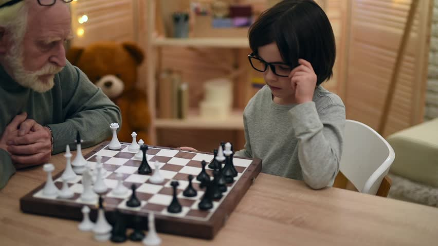 Little boy in glasses, pondering the strategy, plays with elderly man in chess. Old grandfather plays chess with smart grandson. Game of chess.