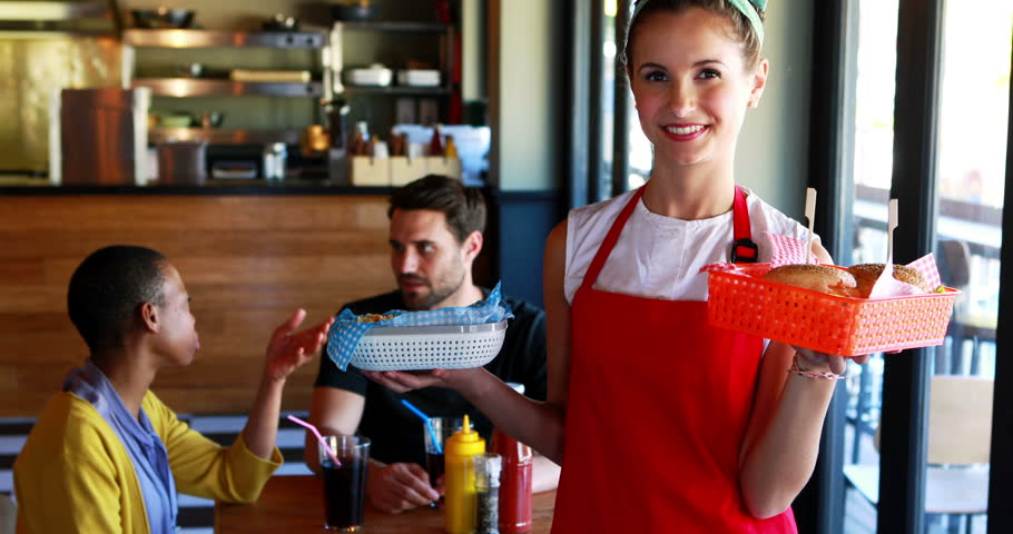 Portrait of a waitress holding burger and french fries in tray in a restaurant, customers in background