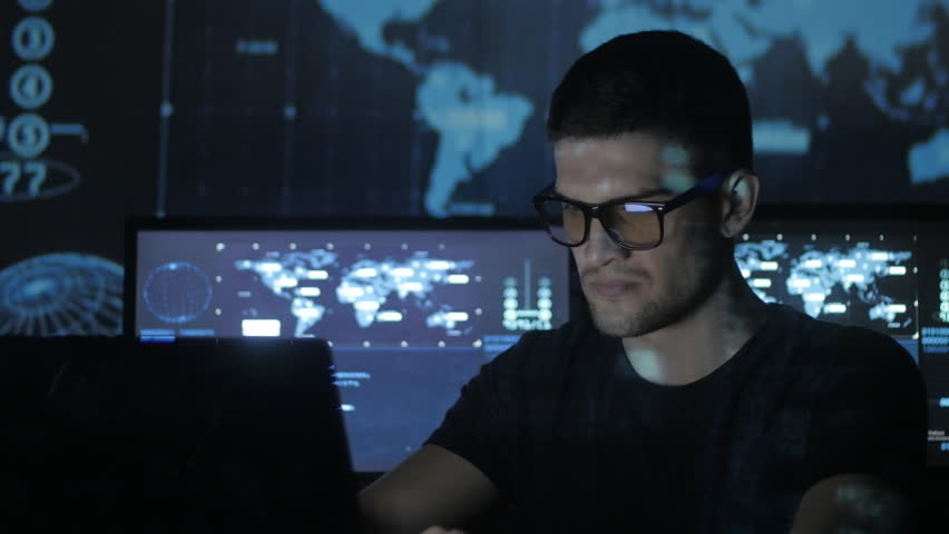 Hacker programmer in glasses is working on computer while blue binary code characters reflect on his face in cyber security center filled with display screens. | Shutterstock HD Video #1008776843