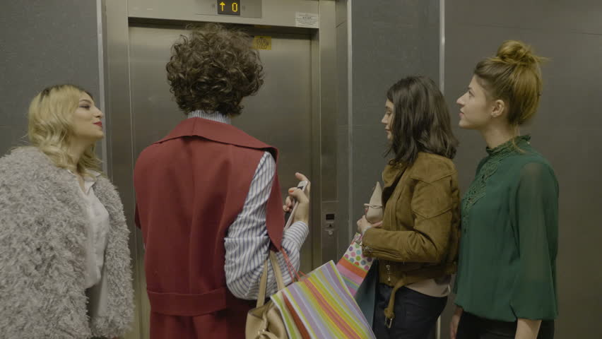 Group of female managers friends holding shopping bags and using elevator to reach the first floor | Shutterstock HD Video #1008792143