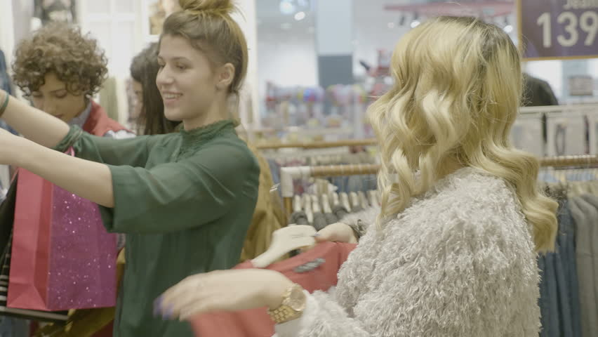 Happy styled multicultural mixed race female friends checking a designer bag an looking at clothing items to shop in a brand store at the mall | Shutterstock HD Video #1008792203