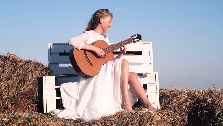 Girl playing the guitar. Fragment. Woman playing guitar on sunset. | Shutterstock HD Video #1008799253