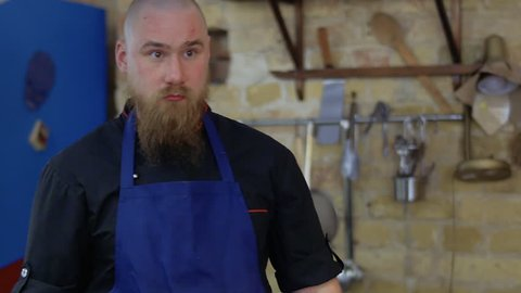 Portrait of serious chef with scars on face and with knife in hands