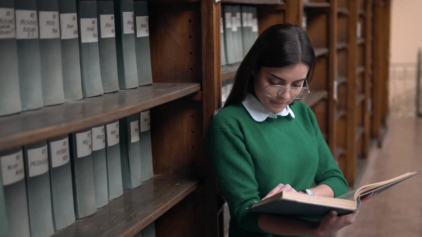 Happy girl dreaming while reading old gray book, beautiful brunette in glasses standing with book before bookshelves in study hall