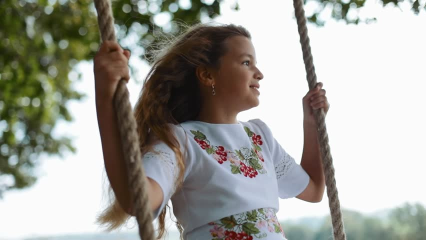 Rotation view of a beautiful little girl in a nice white embroidered dress sitting on a wooden swing seat in the orchard. Summer vacation, positive emotions, cheerful mood. Slow motion, child portrait
