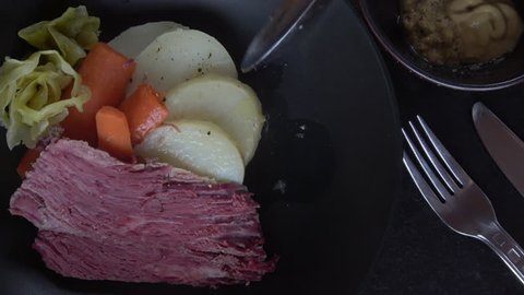 Corned Beef and Cabbage with Mustards. Served on a black plate.