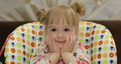 Beautiful two years old girl smiling and making hide and seek with her hands. Cute blonde child. Brown eyes. Close up