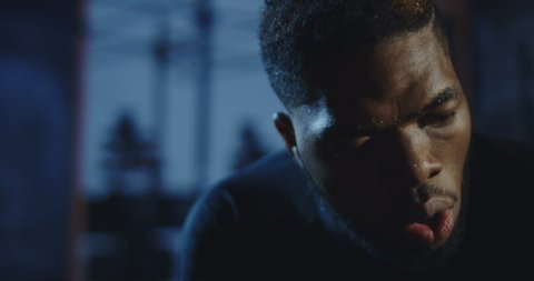 4K slow motion shot of focused African-American man in sportswear breathing deep trying to recover after heavy workout. Shot on Red cinema camera.