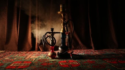 Hookah hot coals on shisha bowl making clouds of steam at Arabian interior. Oriental ornament on the carpet. Stylish oriental shisha in dark with backlight. Shisha on rotating display. Slider shot