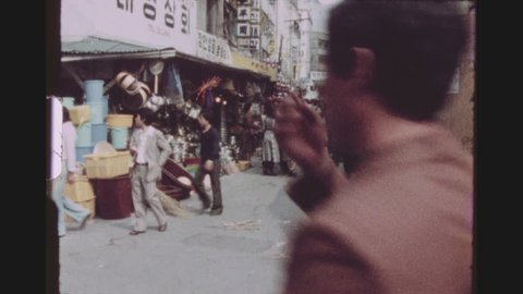 SOUTH KOREA, SEOUL, APRIL 1977. Panning Shot Over A Busy Shopping Street Corner With Many Stores, Shoppers And Passerby.