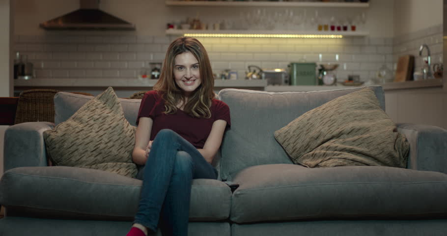 Young, attractive woman sits down on a couch and turns on the television using a remote control. | Shutterstock HD Video #1008851183