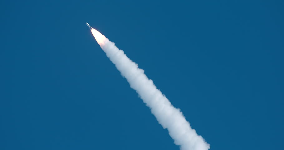 Classic shot of Space Rocket flying through deep blue sky with bright flames and a nice trail of white exhaust smoke. 4K at 120 fps slow motion.