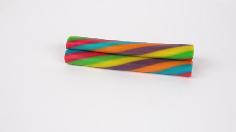 Colourful soft licorice jelly candy sticks rotating on turntable. Isolated on white. Loopable.